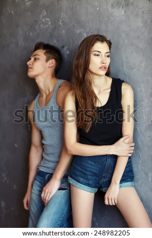 fashion beautiful young couple in quarrel on grey wall background  - stock photo