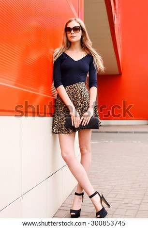 Fashion beautiful young woman model in leopard skirt and sunglasses with handbag clutch over red background - stock photo