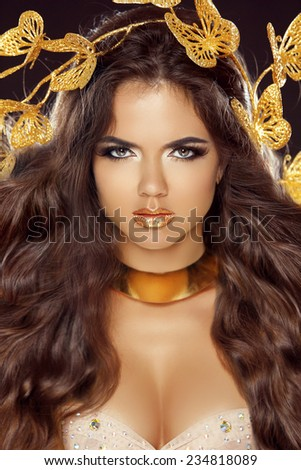 Fashion Beauty Brunette Girl Portrait with makeup and long wavy healthy hair. Isolated on black Background. Glamour Makeup. Gold Jewelry. Hairstyle. - stock photo
