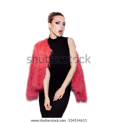 Fashion Beauty female model wearing black dress and pink fur coat. Gorgeous young Woman Portrait. Stylish Haircut and Makeup. Vogue style studio shot on white background not isolated - stock photo