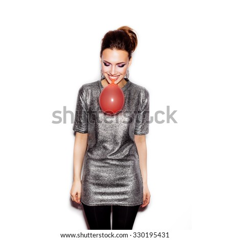 Fashion Beauty Girl blowing a red balloon. Gorgeous Woman Portrait. Stylish Haircut and Makeup. On White background no isolated  - stock photo