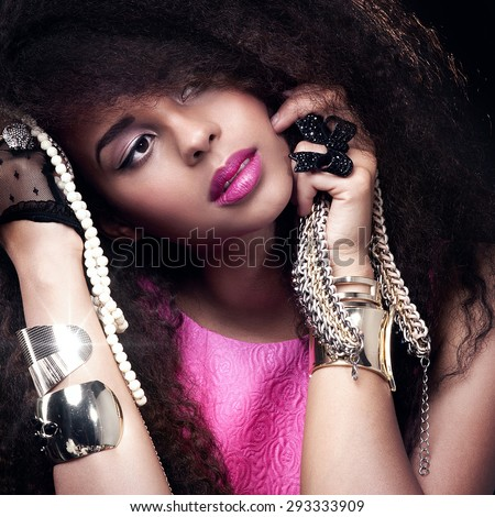 Fashion beauty girl posing in studio. Sexy young woman holding jewelry. Girl with long healthy hair. - stock photo