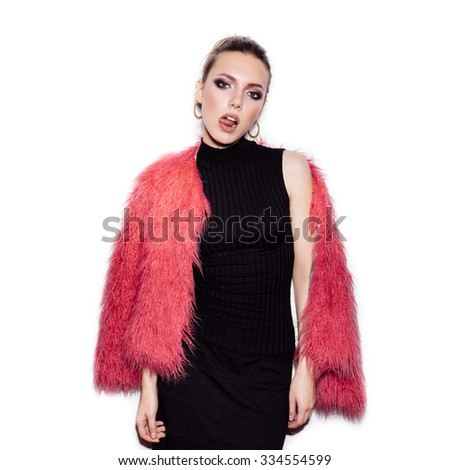 Fashion Beauty Girl wearing black dress and pink fur coat. Gorgeous young Woman Portrait. Stylish Haircut and Makeup. Vogue style studio shot on white background not isolated - stock photo