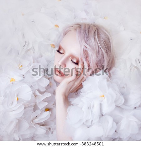 Fashion Beauty Model Girl in white Roses. Surrounded by flowers, background. Bride. Perfect Creative Make up and Hairstyle.