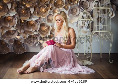 fashion beauty model girl with flowers on the background. Perfect Creative Make up. Beautiful girl in dress with book.