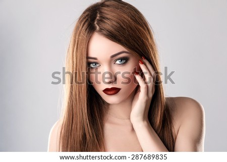 Fashion Beauty Model. Sexy Young Woman on Grey Background. Red Matte Lips and Nails. Pure Beauty. - stock photo