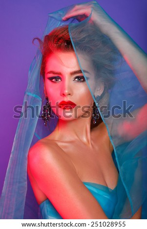 Fashion beauty model with evening art make up and hair, red light, color background. Studio shot. Blonde.