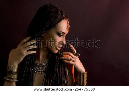 Fashion Beauty. Mystic eastern Make-up. Beautiful Woman With Luxury glossy gold Makeup and stylish hair (dreadlocks) . Beautiful sensitive Girl Face, indian accessories (oriental jewelry) - stock photo
