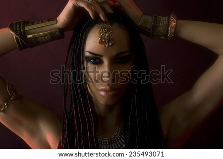Fashion Beauty. Mystic Make-up. Beautiful Womans With Luxury glossy gold Makeup and stylish hair (dreadlocks) . Beautiful sensitive Girl Face, accessories - stock photo