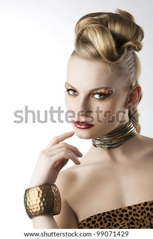 fashion beauty portrait of blond young cute girl with creative hair style and leopard make up, she is turned of three quarters looks in to the lens and has the right hand near her mouth - stock photo