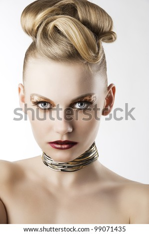 fashion beauty portrait of blond young cute girl with creative hair style and leopard make up, she is in front of the camera and looks in to the lens - stock photo
