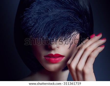Fashion beauty portrait of nude sexy brunette woman with silky bob hairstyle on dark. Sensual lady mysteriously looks, covering eye by black feather. Girl with luxury makeup, red lips. Face closeup - stock photo