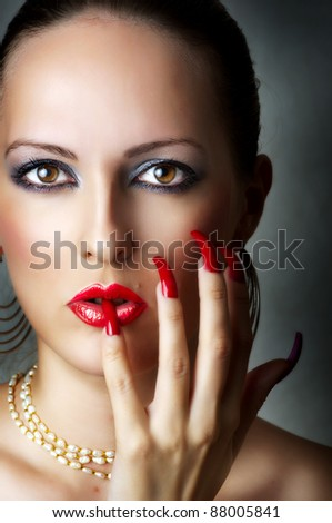 Fashion beauty portrait of young sexy model female face with glamour make-up for party - red glow lips and smoky eyes. Seductive woman with pearl necklace and stylish long nails - stock photo