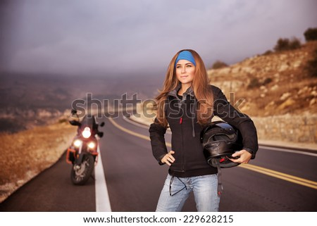 Fashion biker girl standing on the road with helmet in hands, traveling in overcast weather, active lifestyle concept - stock photo