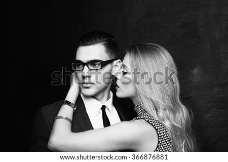 fashion black and white  studio photo of sexy impassioned couple. handsome businesslike man in glasses posing with  beautiful girl with blond hair