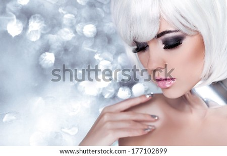 Fashion Blond Girl. Beauty Portrait Woman. Holiday Make-up. Snow Queen High Fashion Portrait over Blue bokeh Background. - stock photo