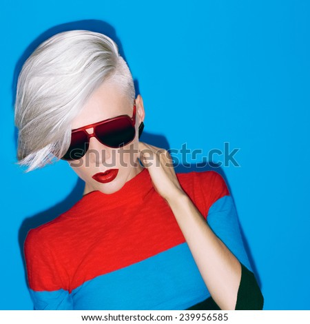 Fashion blond lady with trendy hairstyle and sunglasses on  blue background - stock photo
