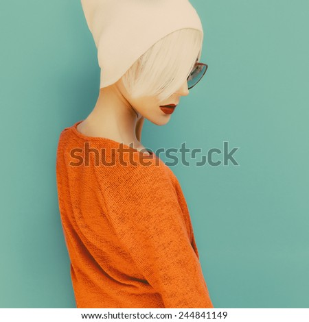 Fashion Blond model with trendy Cap and Sunglasses on blue background - stock photo