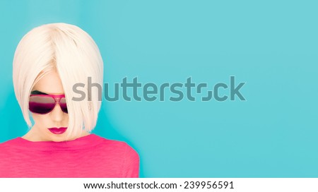 Fashion blond model with trendy Haircut and Sunglasses on blue background - stock photo