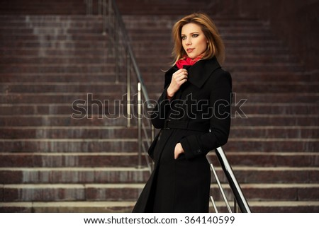 Fashion blond woman in black coat on the steps - stock photo