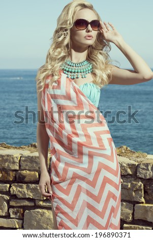 fashion blonde female in vacation. Posing with cute summer style, pareo on bikini, sunglasses and big turquoise neckalce - stock photo