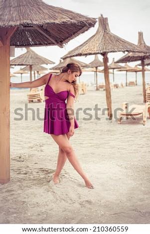 Fashion blonde happy at the sea posing sensual shoe-less on sand under tiki patio umbrella dressed in a fuchsia pink dress - stock photo