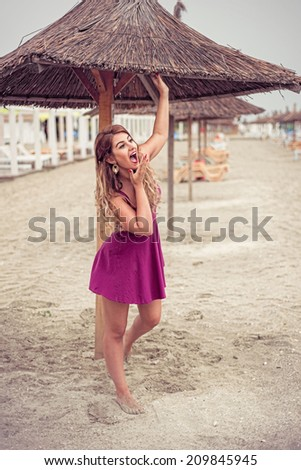 Fashion blonde happy at the sea posing shoe-less on sand under tiki patio umbrella dressed in a fuchsia pink dress holding hand at her mouth - stock photo