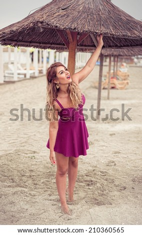 Fashion blonde happy at the sea posing shoe-less on sand under tiki patio umbrella dressed in a fuchsia pink dress looking for rain - stock photo