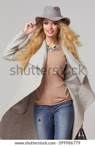 Fashion blonde model in nice clothes posing in the studio. Wearing coat, hat, handbag, ripped jeans  - stock photo