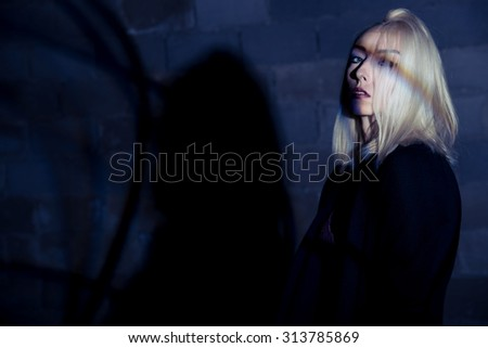 Fashion blonde slim girl at the dramatic light