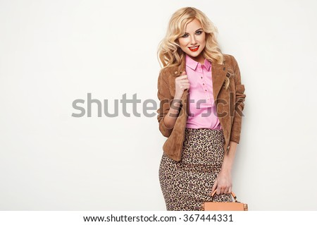 Fashion blonde woman in stylish clothes posing in the studio, holding handbag  - stock photo
