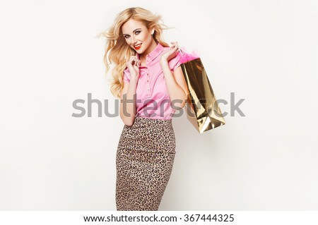 Fashion blonde woman in stylish clothes posing in the studio holding shopping bag  - stock photo