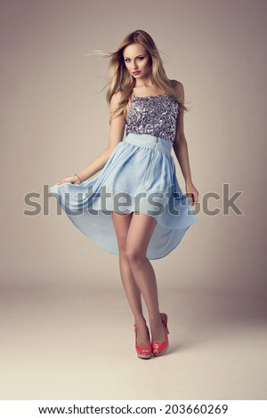 fashion blonde woman wearing ethereal skirt, glitter top and high heels - stock photo