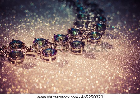 Fashion bracelet with mystic topaz, rainbow topaz on filtered glittering background.