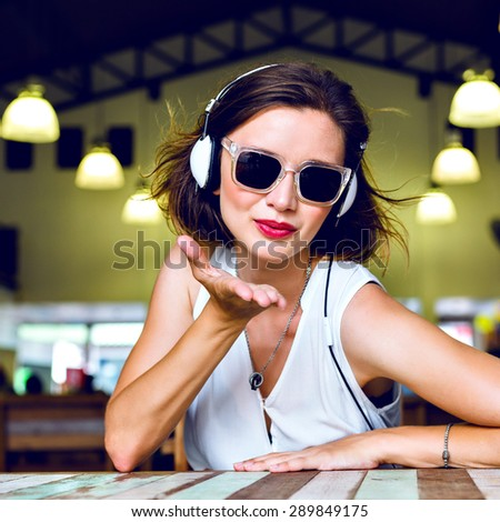 Fashion bright portrait of stunning happy woman sending air kiss, having fun, listening music on her headphones, toned colors. - stock photo
