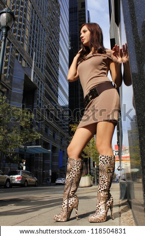 fashion brunette girl in sexy boots posing in big city, urban outfit with leopard shoes and short brown dress
