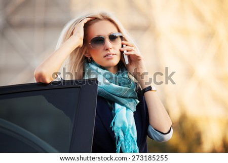 Fashion business woman calling on the phone by her car