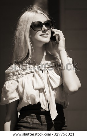 Fashion business woman in sunglasses calling on mobile phone - stock photo