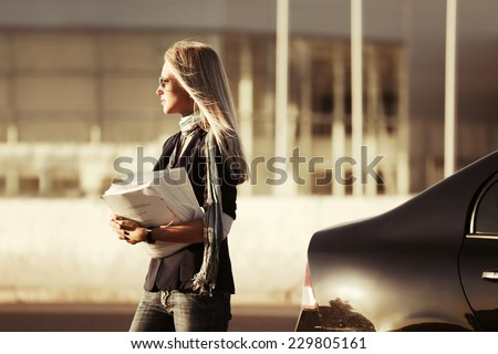 Fashion business woman with financial papers at the car  - stock photo