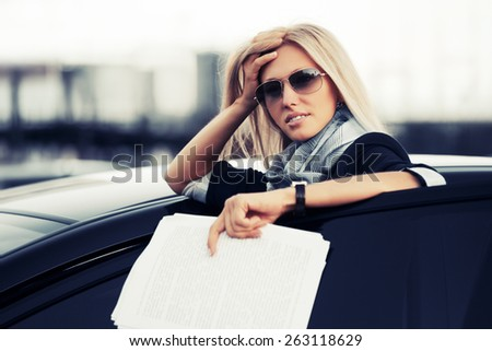 Fashion business woman with financial papers by her car  - stock photo