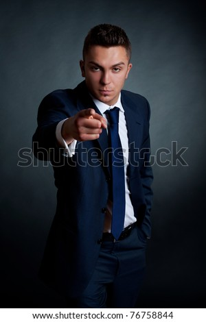 fashion businessman pointing at the camera on a dark background
