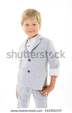 fashion cheerful little boy in gray suit posing at studio over white