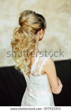 Fashion close up back portrait of attractive young bride with long curly hair in morning of wedding day. Hairstyle. Glamour Makeup. Fashionable blonde girl posing, looking away - stock photo