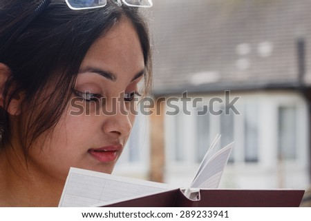 Fashion close up of a young woman reading a book