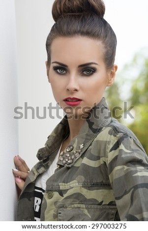 fashion close-up outdoor portrait of charming woman with dark make-up. creative hair-style and urban military shirt, looking in camera  - stock photo