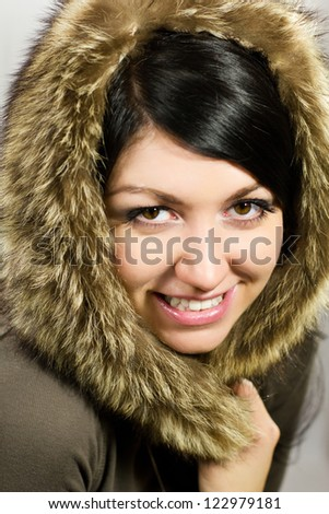 Fashion close up portrait of a young pretty girl with a fur around her face