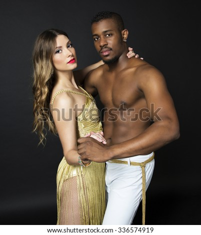Fashion close up portrait of attractive dancing couple. Hugging, holding hands. Dancing latino. Passion. Sensuality. The girl's perfect skin facial make-up and long curly hair. The guy's pumped abs