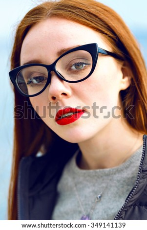 Fashion close up portrait of young student teen hipster pretty girl wearing coat and sweater, clear glasses, red lips, winked skin, winter cold time.