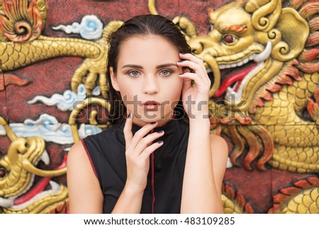 Fashion closeup portrait of young brunette woman over golden dragon on the wall background