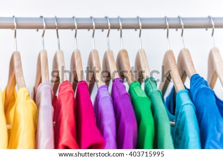 Fashion clothes on clothing rack - bright colorful closet. Closeup of rainbow color choice of trendy female wear on hangers in store closet or spring cleaning concept. Summer home wardrobe. - stock photo
